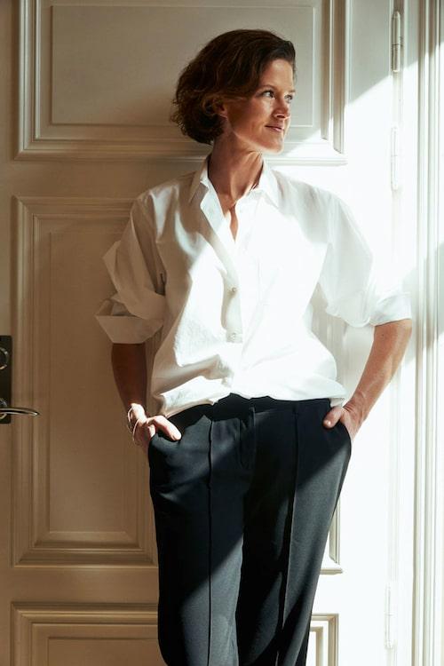 Anna Kinberg Batra i en skjorta från Acne Studios och kostymbyxor från Stylein. Armbanden kommer från Caroline Hjerpe.