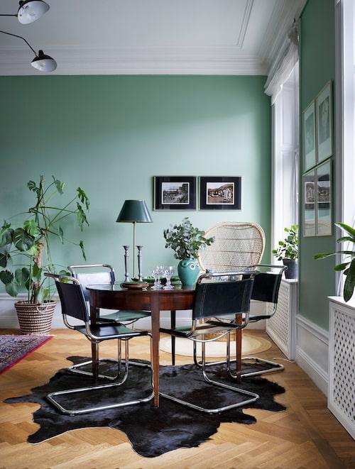 Utanför vardagsrumsfönstren myllrar stadslivet vid Odenplan. Komatta från Ikea. Korgstolen köptes på Blocket, matbordet, liksom stolarna från Fasem Italy, köptes på Bukowskis. Golvlampan från Ikea har fått ny skärm från en antikaffär. Fotografier av Hongkong som det såg ut i början av 1900-talet. Grön vas, arvegods efter saknad mormor.