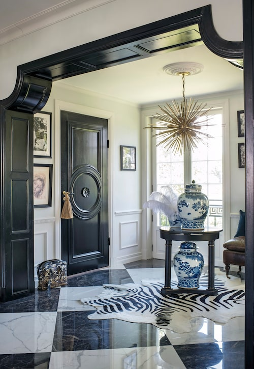 Elegant avfasad valvöppning och schackrutigt marmorgolv i den pampiga hallen. Lampa Strada, Kelly Wearstler, och kinesiska urnor köpta i New York. 20-talsdörren kommer från Nacka byggnadsvård.