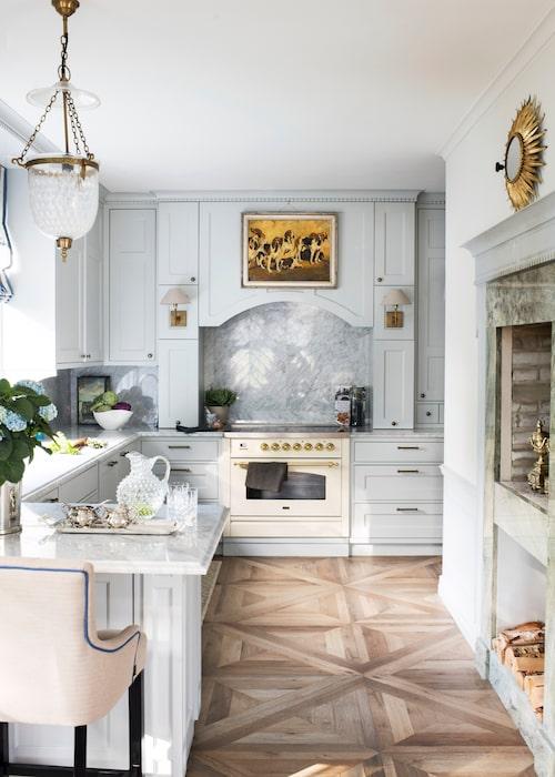 Caroline ville att köket skulle kännas som ett vardagsrum och ritade det själv. Spis, Ilve, carraramarmor lagt i chevronmönster ovanför. Till höger platsbyggd öppen spis. Italienskt keramikgolv, Kakeldax. Barstol, Homeline.