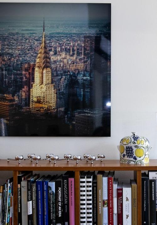 """Foto av Laurent Dequick från favoritstaden New York, """"Där finns så mycket inspiration att hämta"""", säger Pekka. På bokhyllan aluminiumljusstaken Constella från Klong och Birger Kaipiainens klassiska karott i serien Paradis för Arabia. """"Jag har alltid älskat finskt glas och porslin"""", säger Pekkas make Erik."""