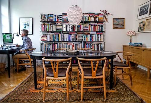 """""""Jag har verkligen drömt om en matsal med bibliotek"""", säger Pekka, som förvarar de redan lästa böckerna här, och de fortfarande olästa på hyllor i sovrummet. Malmstenskrivbordet vid fönstret är auktionsfyndat, då med ytskador, men Erik lät sprutlackera det. Även Wegners Y-stolar är från auktion liksom mattan från Afghanistan. Taklampan Balmoral är köpt på R.o.o.m. Bredvid Pekka en tavla av legendariska kostymören Mago som Erik arbetat med."""