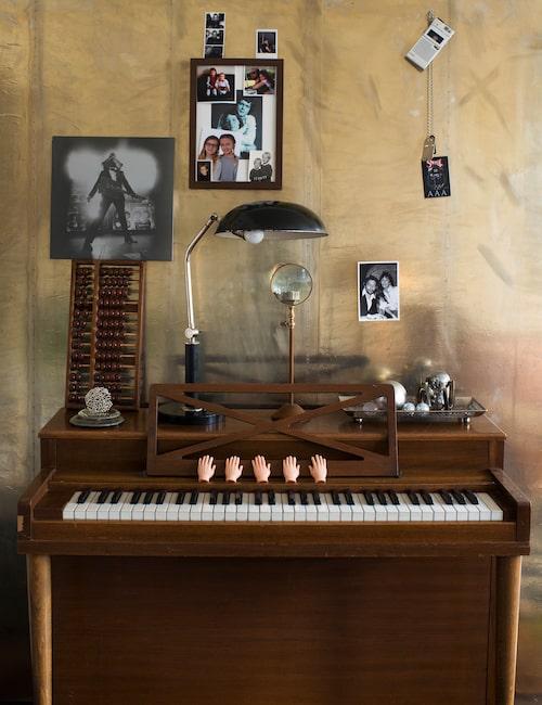 Zinkplåten bakom det lilla pianinot är egentligen en sänggavel. Pianinot har två strängar per tangent i stället för pianots tre och får en speciell klang. Bland alla foton på väggen syns en blåtonad bild mitt i den svarta ramen. Det är Klas Åhlunds mor och far.