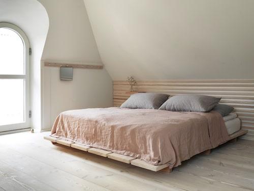 Den träklädda väggen, sängbord och sängstomme är alla specialdesignade och tillverkade i douglasgran från Dinesen.
