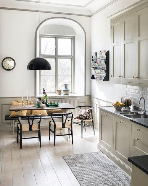 Köket från Kvänum fanns på plats när Elisabeth och Lars flyttade in, likaså skivorna av svart granit. Matbordet och bänken är antika, kompletterade med Wegners Y-stolar. Taklampan är Marcel Wanders takstuckaturinspirerade (på insidan) Sky garden för Flos.