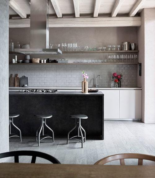 """Tonalitekaklet över bänken avviker en smula från den grå-svart-bruna omgivningen med sin """"tortora""""-färg (duvblått). Köket är från Modulnova och hyllorna är gjorda av en snickare i byn. Fläkt, Franke, gasspis, Foster. Barstolar i järn, Maisons du monde. Det kombinerade köket och matsalen är husets enda rum med trägolv."""