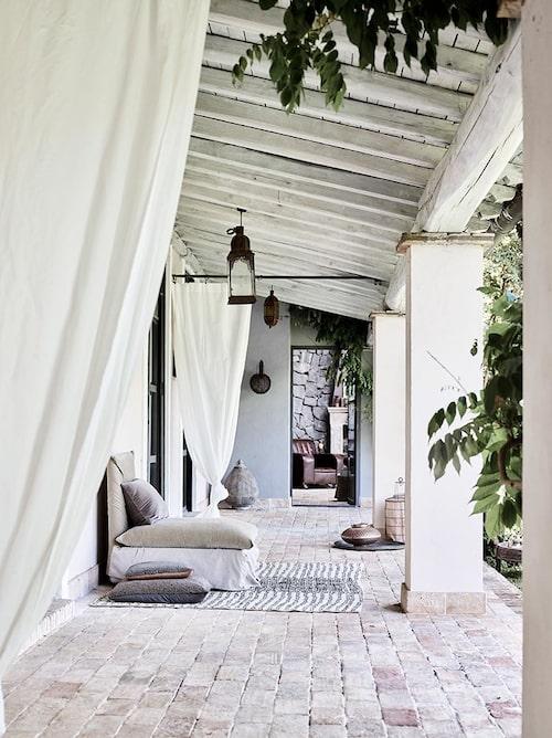 Den taktäckta delen av pation delas av med vita Ikeagardiner. Taklyktorna hittade Hanne i Marrakech och mattan i Turkiet. Saccokuddarna är hongkongköp och lyktan från Bangkok.