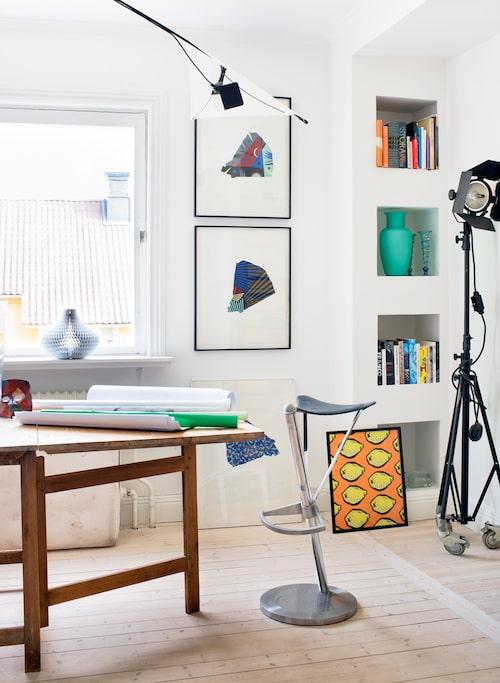 Slagbordet i studion fick Louise av en dam på Öland. Stolen är spanskt 80-tal, taklampan en prototyp av Ingo Maurer. Grafik av Rune Söderqvist, citron-motiv, loppis. Fotolampan hängde med från ateljén på gården.