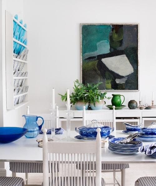 """Vitt och blått är Louises färger, den saken är klar. """"Men grönt och turkos tycker jag också är härligt ihop."""" Kring superellipsbordetstår arbetarstolar formgivna av Carl Westman 1899. Porslin, Wedgwood, servetter, Le Jacquard Français, glas och tillbringare köpta i franska Biot. På sidobordet av Carl-Axel Acking, Ikea-krukor och grön keramik från Biot. Oljemålning av Lars Wellton."""