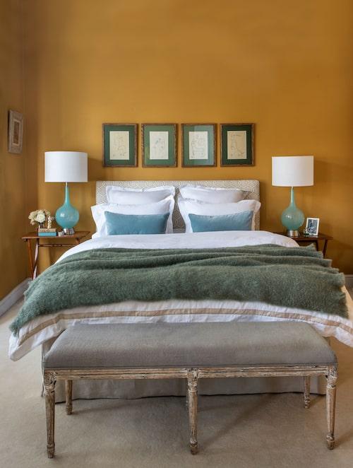 Bänk i gustaviansk stil, och turkosfärgade lampor från 1960-talet i fin kontrast till väggen målad i den mustiga kulören India yellow från Farrow & Ball. Ovanför sänggaveln hänger fyra provtryck av litografier signerade Jean Cocteau och Henri Matisse.
