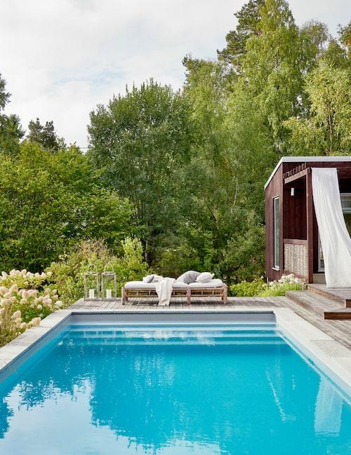 Varma, soliga sommar-dagar sitter man behagligt vid swimmingpoolens