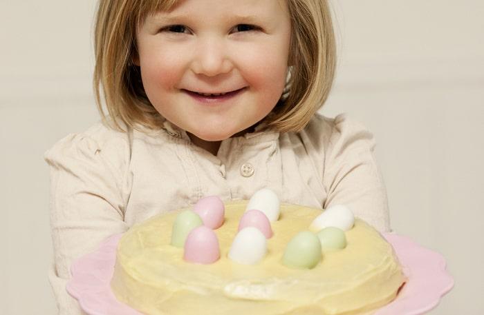 En mandelkaka med vit chokladfrosting, dekorerad med godisägg, blir den perfekta avslutningen på påskmiddagen.