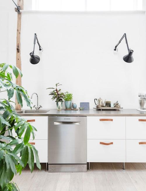 Vita fronter, rostfri bänkskiva och läderbeslag – skandinavisk köksstil i sin renaste form.