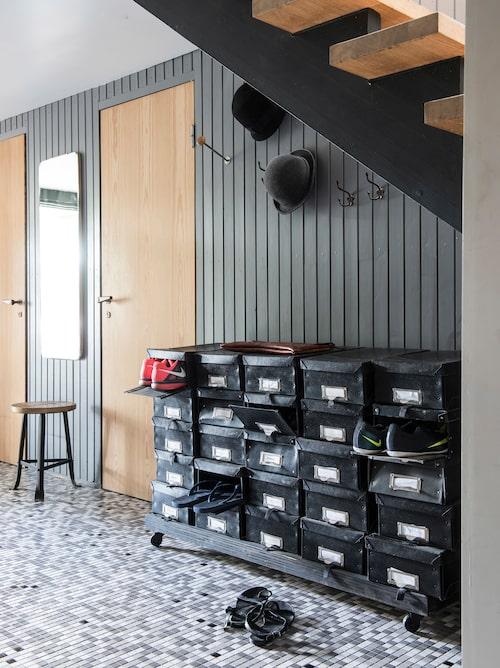 Bo för sko. Under trappan bor familjens skor i lådor från Granit. Många skor blir det med tre söner. Notera det vackra mosaikgolvet som är original.