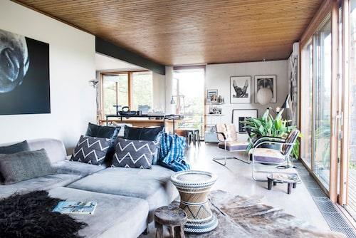 Ljusdusch extra allt. I vardagsrummet är det tydligt hur nära inpå naturen huset ligger och hur tätt samspelet är. Via skjutdörrarna som går från golv till tak kommer du ut på terrassen. Textilierna är en skön mix av inköp från Sverige och Sydafrika