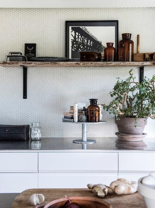På köksbänken och hyllan står bruna apoteksflaskor som Anett fyndat på loppisar. Det höga kakfatet som rymmer smått och gott är från en av Granits tidiga kollektioner.