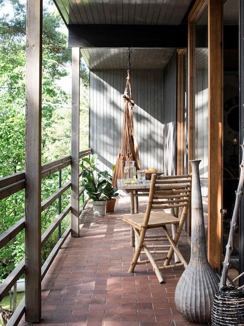 På den långsmala terrassen lever Anett en stor del av tiden under sommarhalvåret. Skjutdörrarna står oftast öppna. Gunga från Ikea. Bord, stol och vas från Granit.