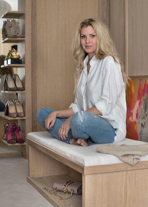 Pallen mitt i dressingrummet har inbyggd belysning och sko- eller väskförvaring på båda sidor. Bakom Caroline skymtar hennes flammande målning Future.