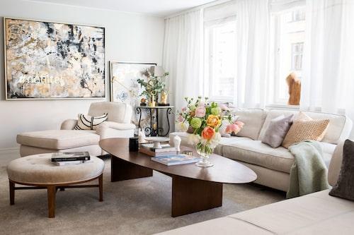 Bara runda former för att mildra lägenhetens kantighet: Ovalt soffbord, specialbeställt i valnöt, soffa och fåtölj från Mio, pallen fick Caroline i present av sin mamma. På väggen neon-ljus-målning No filter och på golvet kvinnomotiv Vera, båda av Caroline Tamm.