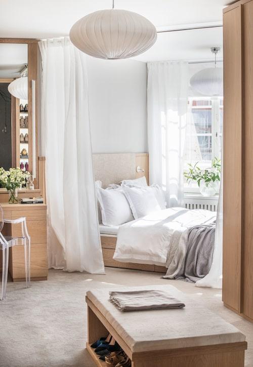 """All inredning i Carolines kombinerade sovrum/dressingroom är byggd i vitoljadek av finsnickaren Henrik Falk. Sängen krymptes till 180 cm-längd och gick precisin i burspråksnischen. Vita gardinvåder, Ikeas Vivan, ramar in och separerar.""""För att inte skrivbordsstolen skulle ta något av rymden i rummet valde jagKartells genomskinliga Ghost."""""""