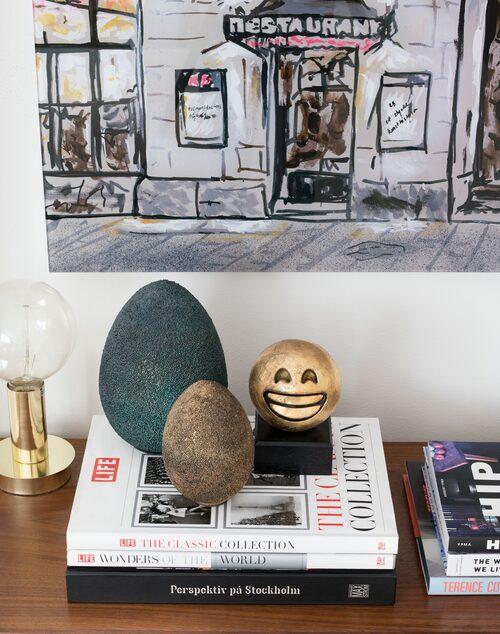 Guld-emojin Happy har Caroline gjort, men äggen köpte hon på Posh living. Ovanför, detalj från hennes målning Nearby från KB-huset i Stockholm, överförd till print på plexiglas.