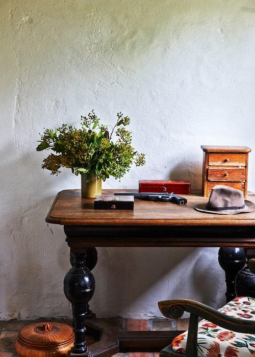 I biblioteket står ett tyskt barockbord inropat på Göteborgs auktionsverk. Stilleben med låsbara små skrin och ett gammalt handeldvapen.