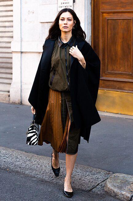 Street style inspo - så bär du den plisserade kjolen i höst: med tunna strumpbyxor, högklackade skor och elegant lång kappa.