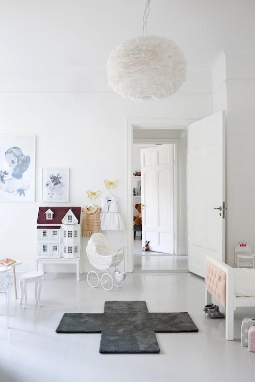 """Högt i tak, lätt och luftigt i Belles rum. Dörren i bakgrunden leder in till Matteos rum, i hallen emellan finns garderober och badrum. I båda barnrummen finns inbyggda garderober som rymmer mycket. """"Vi har absolut mer förvaring än leksaker!"""", säger mamma Lisa nöjt. Taklampa Eos L, från Vita, på golvet mattan Crux, Asplund. Dockskåp, Minimi's smått & sånt. Posters, Mrs Mighetto, dockvagn, Eurotoys."""