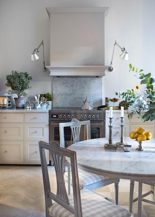 Ett lantligt drömkök. Köksfronterna är byggda av snickeri till befintliga stommar från Ikea. Fläkten är inbyggd bakom spiskåpan och ramas in av ett par vägglampor, Tolomeo micro från Artemide. Spis, Bertazzoni. 1700-talsstolarna är arvegods, bordet är nybyggt efter Carolines ritningar med underrede av stål och skiva av carraramarmor.