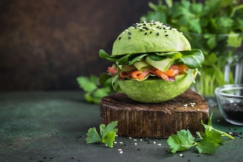 healthy raw avocado burger with salted salmon and fresh vegetables.  selective focus,