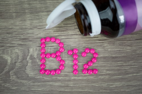Pink pills forming shape to B12 alphabet on wood background
