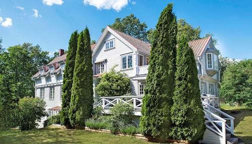 """Den äldre delen av huset döljs delvis bakom de jättelika cypresserna som Camilla och Michael planterade i slutet av 90-talet. """"Det var inte tänkt att de skulle bli så stora"""", säger Camilla. Till vänster syns utbyggnaden, som är på 200 kvadratmeter i tre plan."""