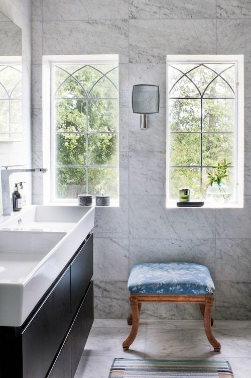 """Badrummet i carraramarmor ligger i den gamla delen av huset och är nyligen omgjort. De blyinfattade fönstren är original. """"Från början såg man bara ett av fönstren inifrån. Det andra var inbyggt i en garderob i det som tidigare var vårt sovrum"""", säger Camilla Englesson."""