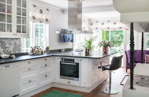 """Köket var två små rum från början men familjen slog ut väggar och skapade ett nytt lantkök. """"Spisen till höger, är ny, den lät jag mura upp när jag sett en likadan på tv. Jag åkte till Nacka byggnadsvård och köpte vedspisen"""", säger Camilla. Det platsbyggda köket, tillverkat av Möbelkvalité Taxinge, har förvaringen i lådor man enkelt drar ut för god överblick."""
