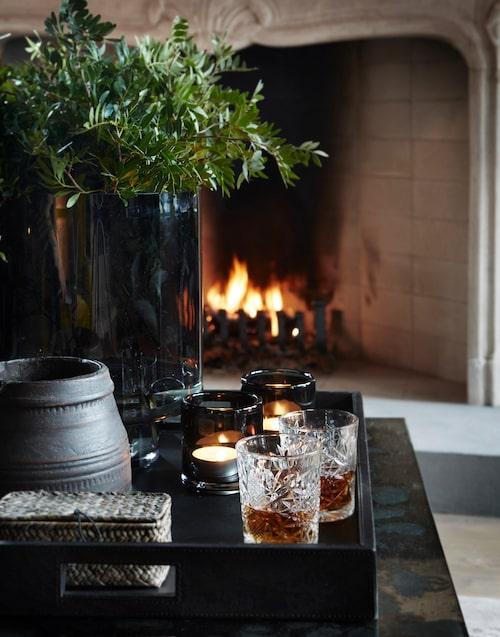 En skål innan tomten kommer. Whiskyn serveras framför den öppna spisen. Glas från Åhléns. Rökfärgad glasvas, bricka och ljuslyktor, Slettvoll.