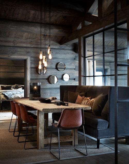Glasväggen har satts in för att skapa mer ljus och rymd runt matbordet. Soffa och kuddar, Slettvoll, bord, Snowdrops, stolar, Sol&luna, taklampa från Buster & Punch. Innanför skymtar parets sovrum.