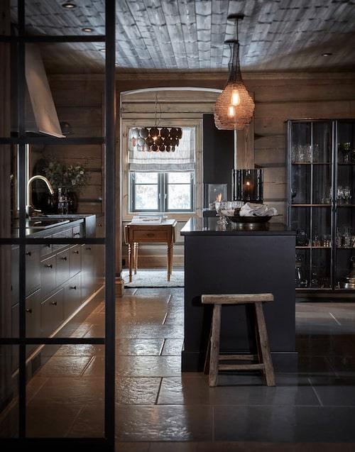 Köket kommer från JH interiör. På golvet ligger kalkstensplattor, bänkskiva av svart granit från Stenprosjekt. Vitrinskåpet kommer från Nordal och lamporna från oslobutikerna Bolina och Objekt.