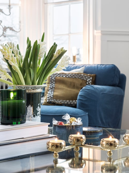 Ett rejält fång vita hyacinter, doftljus och ljusstaken Constella från Klong på glasbordet i vardagsrummet skapar stämning.