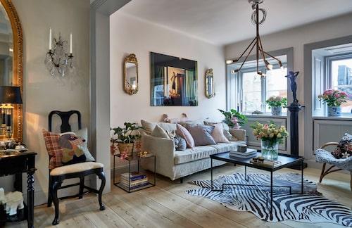 Vindsvåningens öppna ytor har fått en väl balanserad färgskala med grå väggar i matsal och kök. Men vardagsrummets väggar har målats i en puderrosa färg. Soffan kommer från Posh living, soffbord från Fogelmarck, spegellampetter 1700-tal, Thunér antikhandel, fotokonst inköpt på Lumas i Berlin. Kudde med taxmotiv från Svenskt tenn, på golvet ett skinn med tryckt zebramönster.