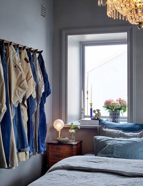 På krokbrädan hänger byxor i färger som matchar inredningen, som en funktionell och dekorativ installation. Sängbordet är från Calles mormor.