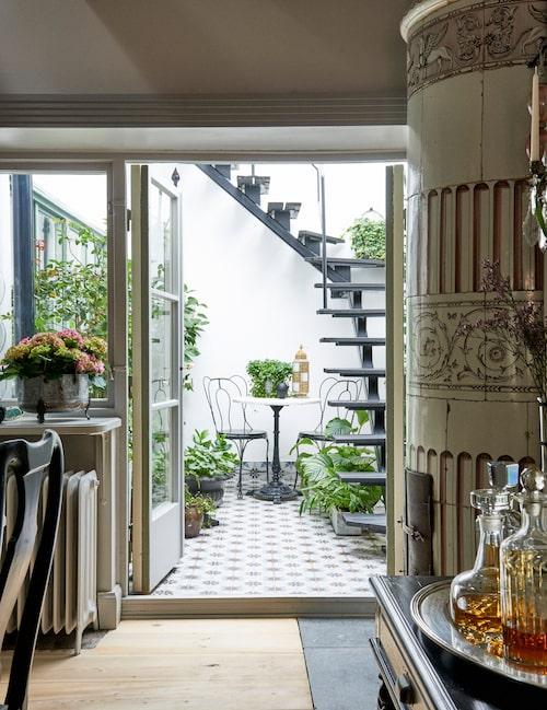 Den mörka trappan mot den vita väggen, och det grafiskt mönstrade marockanska golvet kombinerat med växternas gröna färgskala, ger tydlig karaktär i atriet. Trappan är tillverkad av smed och binder samman den undre terrassen med den övre.