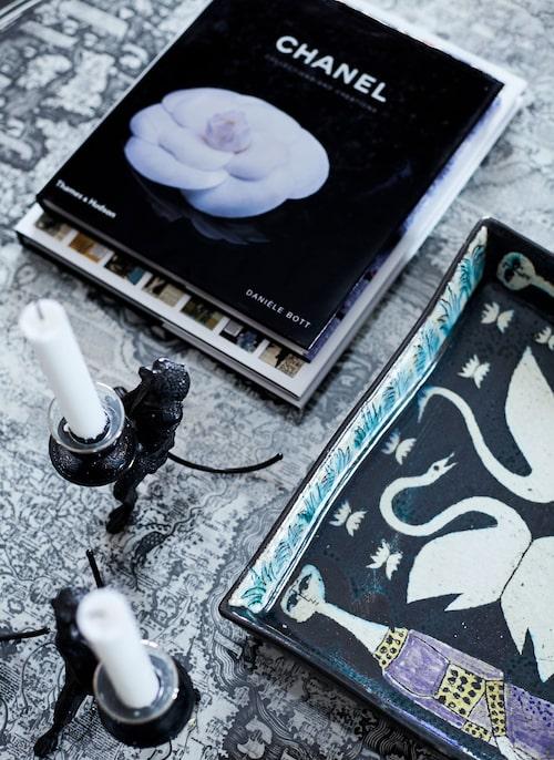 På det runda glasbordet från Svenskt tenn vilar ljusbärande apor från Geco, en smyckesbok från Chanel och ett vackert porslinsfat inropat på auktion.