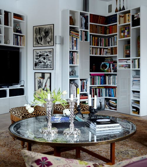 Den platsbyggda bokhyllan sväljer både moderna och antika litterära verk, fotoramar, tavlor och magasin där Grete hittar inspiration. De magnifika ljusstakarna i silver är från Georg Jensen.