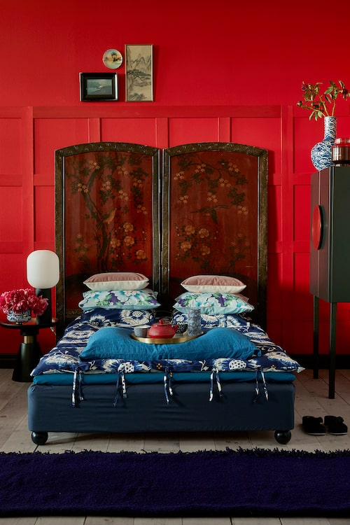 Som sänggavel antik asiatisk vikskärm, Bohemian bird, pionblommig kudde Kenzo, dra-på-lakan på sängbotten, Ikea. Runda sängben Superfront. Sängbord, made.com, blåvit ask med lock, NK Newport.