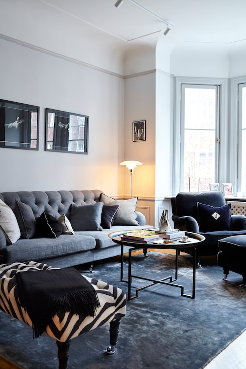 Roy samlar ofta vänner hemma som slår sig ner i den grå djup-häftade soffan från Englesson. Själv dyker han ner i den sammets-klädda älsklingsfåtöljen från samma ställe. Brickbordet är från Svenskt tenn och fotpallen är klädd i tyg från Ralph Lauren.