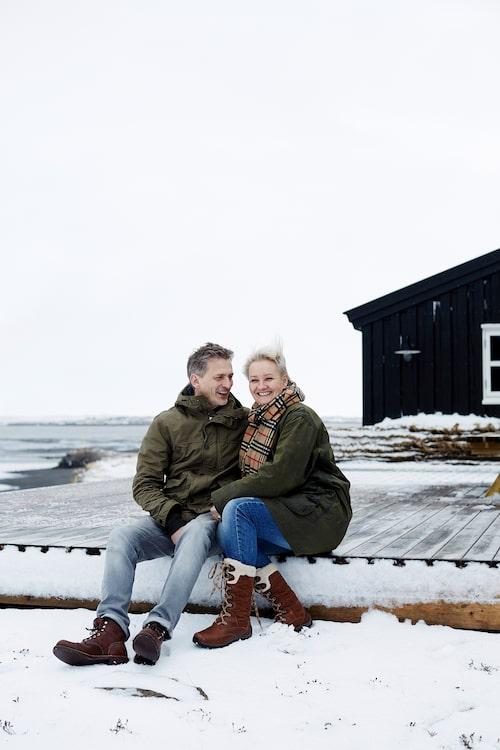 Kristinn och Rut utanför sitt svarta hus i kustbandet.