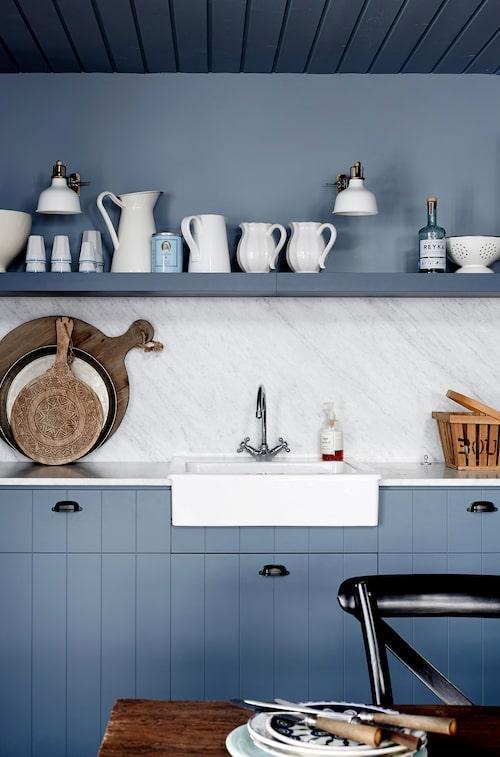 De vertikala linjerna i köksinredningen ger ett lantligt utseende. Arbetsbänk i carrara-marmor, diskho och vägglampor, Ikea.