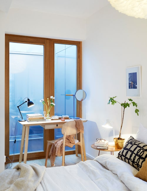Sovrummet har fönsterdörrar i två väderstreck, dessa mot ett ljusschakt. Skrivbord Lisabo, Ikea. Skrivbordslampa, R.o.o.m, spegel, Asplund.