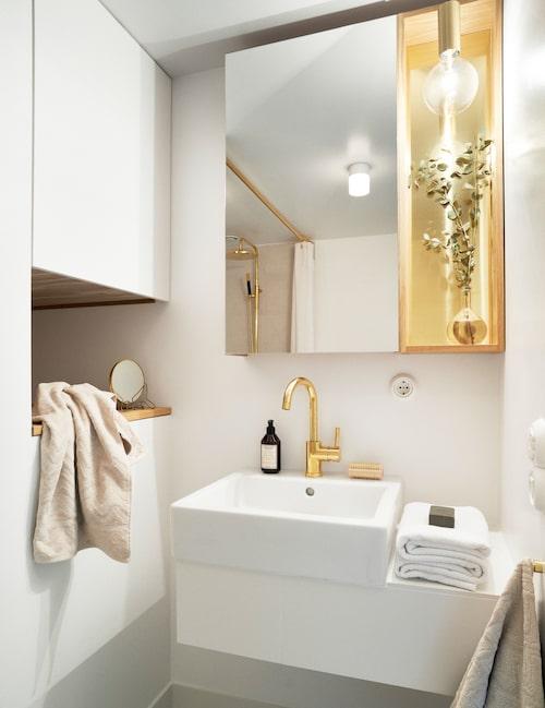 Litet och lyxigt med mässingsdetaljer. Bänken under handfatet är tillverkad av mineralmaterialet dekton, som också återkommer i badrumsgolvet och i bänkskivan i köket. Skåpet till vänster är specialritat och rymmer bland annat tvättmaskin. Blandare Eve, Tapwell.
