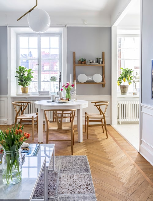 Ljuset strömmar in från de stora fönstrenutmed lägenhetens ena långsida. Soffbord, matta och vägghylla från Bolia. Taklampan är från Flos.